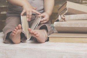 Small feet of a child watching a book